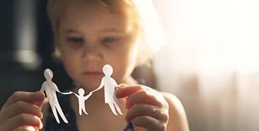 Wat is kindermishandeling - kind speelt met papieren poppetjes en maakt gelukkige familie