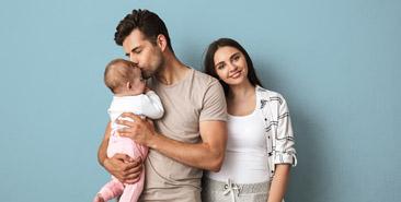 Ouderschap - Vader zoent baby op voorhoofd. Moeder kijkt gelukkig